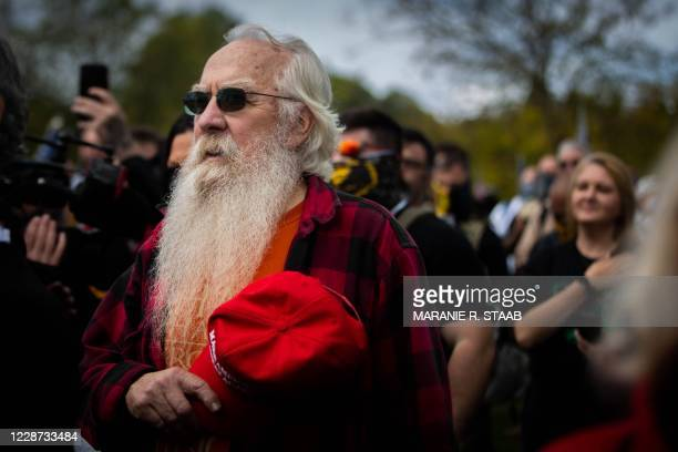 Man hold his hat over his heart while a prayer is said during a Proud Boys rally at Delta Park in Portland, Oregon on September 26, 2020. - Far-right...