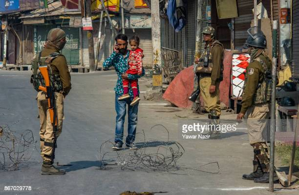 A man hold holds his daughter as Indian paramilitary troopers stand alert on a deserted road during a strike on October 27 2017 in Srinagar the...