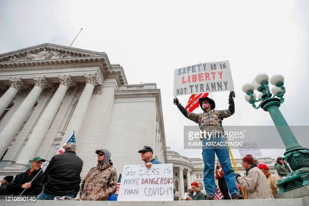 Man hold signs during a protest against the coronavirus shutdown in front of State Capitol in Madison Wisconsin on April 24 2020 Gyms hair salons and...