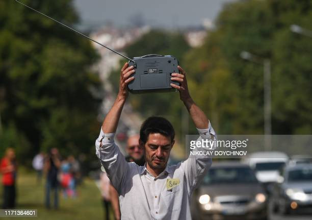 A man hold up a radio as he takes part in a human chain in defense of 'media freedom' around the Bulgarian National radio station in Sofia on...