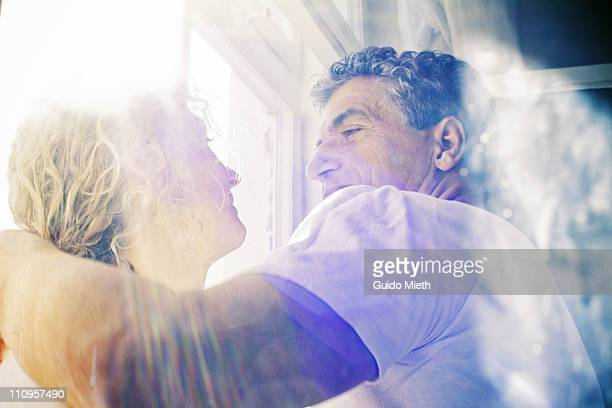 Man holdig his wife while looking into her eyes