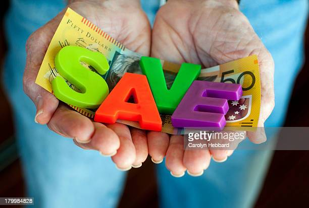 Man Holding $50 with the word SAVE on it.
