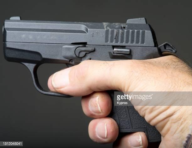 man holding 9mm non-lethal tear gas firing self defense pistol - tear gas fotografías e imágenes de stock