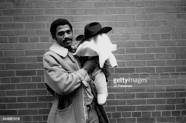 A man holding a baby whose head is covered with a blanket and a cowboy hat USA circa 1975