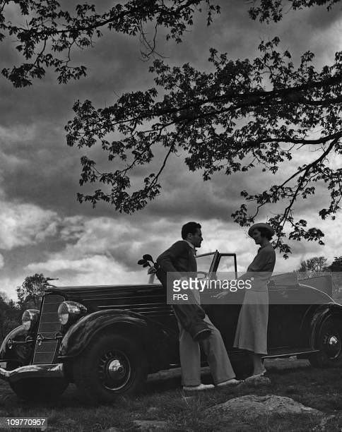 A man holding a bag of golf clubs talking to a woman getting in to her convertible car circa 1940
