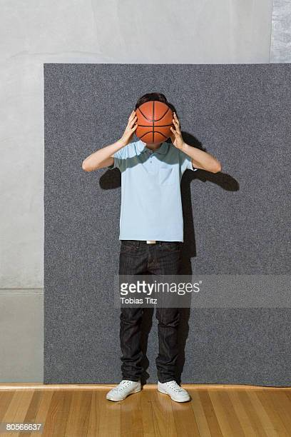 A man holding a basketball in front of his face
