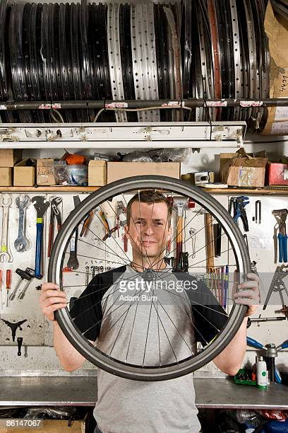 A man holding a bicycle wheel in a workshop
