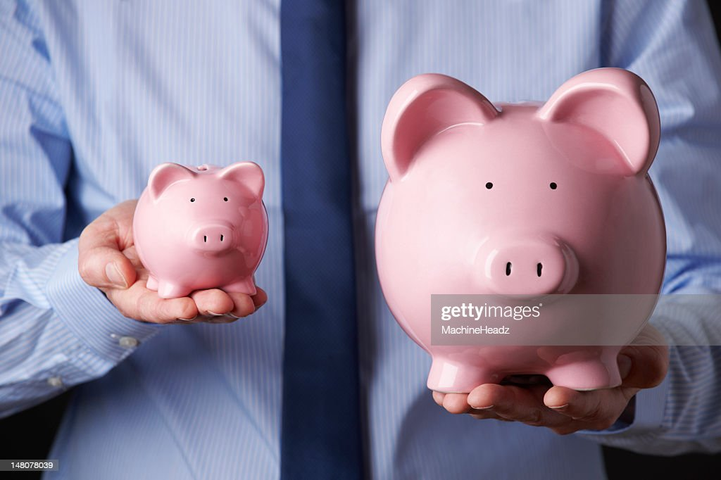 Man Holding A Big And Small Piggy Bank On Each Hand Stock