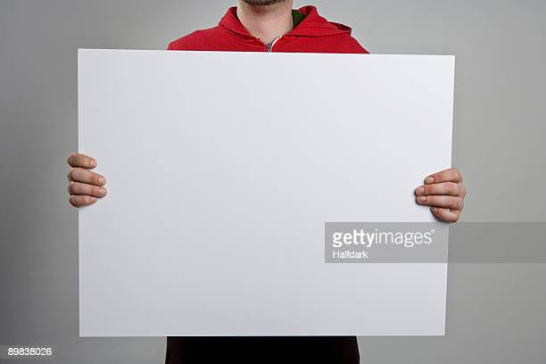 a man holding a blank sign - blank sign stock photos and pictures