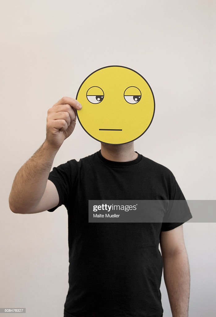 Man holding a bored emoticon face in front of his face : Stock Photo