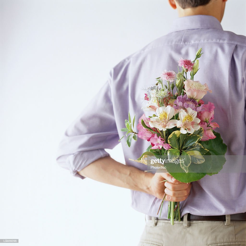 Man Holding a Bouquet of Flowers Behind His Back : Stock Photo