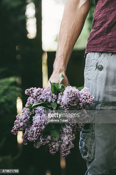 man holding a bouquet of freshly cut lilacs - purple lilac stock pictures, royalty-free photos & images