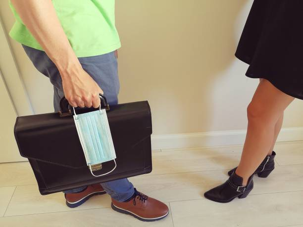 Man holding a briefcase and a surgical mask meets his coworker at office
