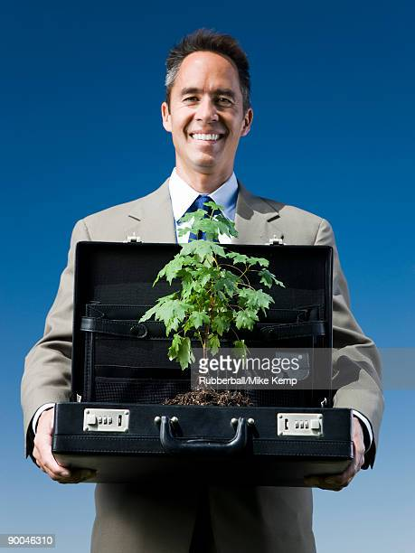 man holding a briefcase with a tree in it