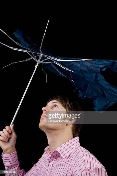 A man holding a broken umbrella