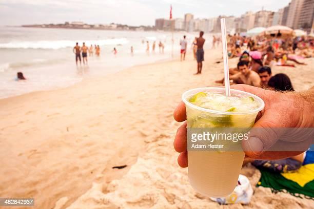 A man holding a Caipirinha on Ipanema Beach.