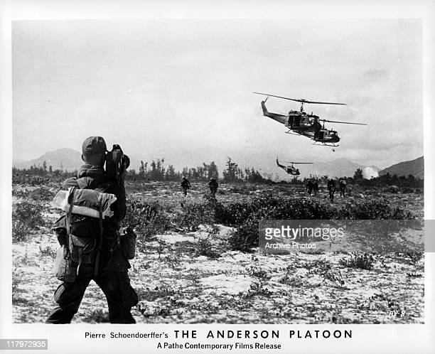 A man holding a camera filming helicopters and soldiers for a documentary 'The Anderson Platoon' 1967