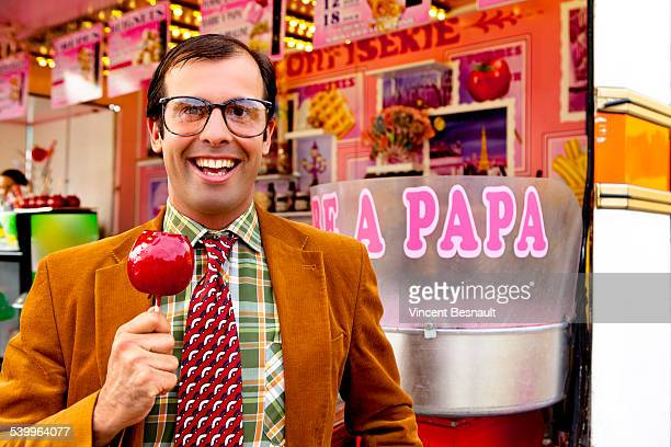 Man holding a candy apple of love at the carnival