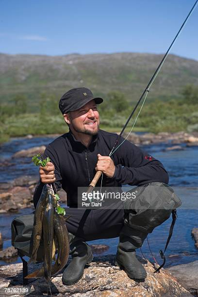 A man holding a casting rod and fish Tarnaby Sweden.