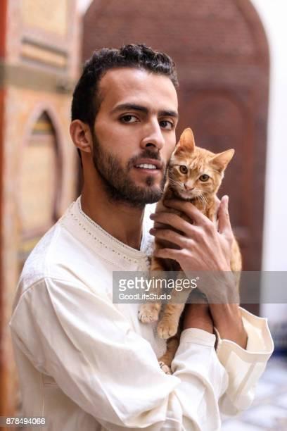 homme tenant un chat - homme marocain photos et images de collection
