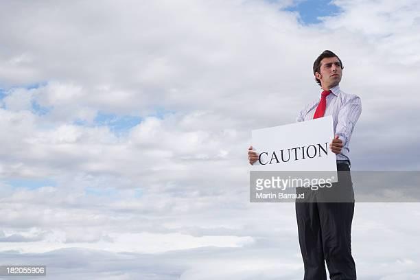 Man holding a caution placard