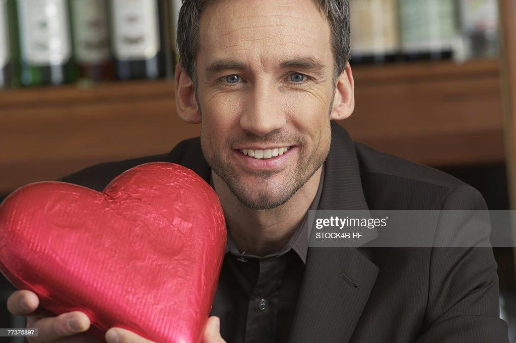 Man holding a chocolate heart : Stock Photo