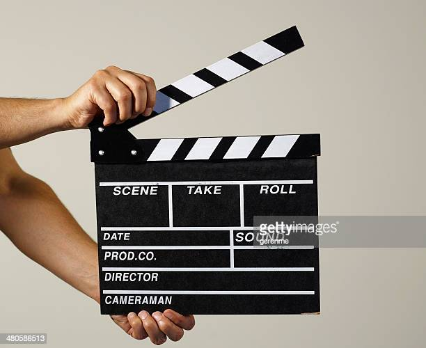 man holding a clapper - clapboard stock pictures, royalty-free photos & images