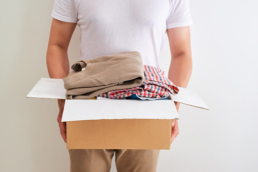 Man holding a clothes donate box. Donation concept. 925211042