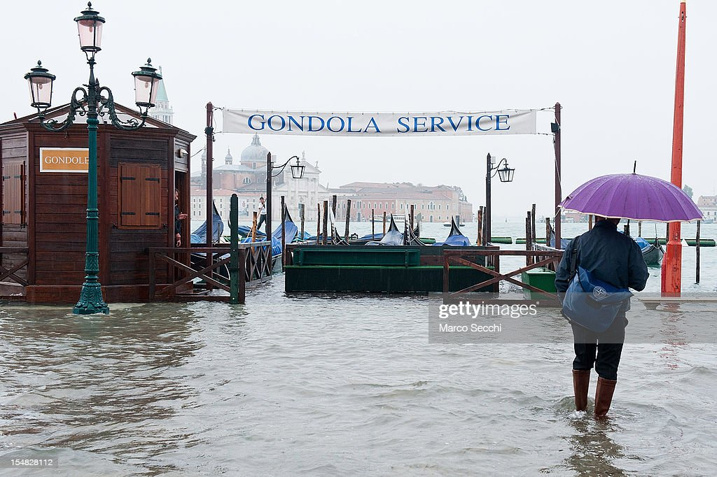 A man holding a colourful umbrella walks ankle-deep in water near St Mark's Square during a high tide on October 27, 2012 in Venice, Italy. The high tide, or acqua alta as it is locally known, stood at 127 centimeters this morning.