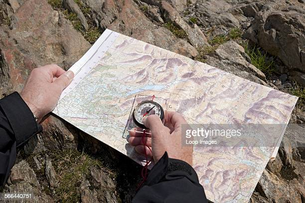 Man holding a compass and a map of the Lake District