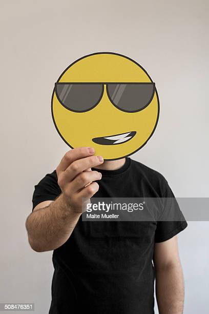Man holding a cool, sunglass wearing emoticon face in front of his face