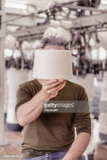 man holding a cotton reel in front of his face in a textile factory - obscured face stock pictures, royalty-free photos & images