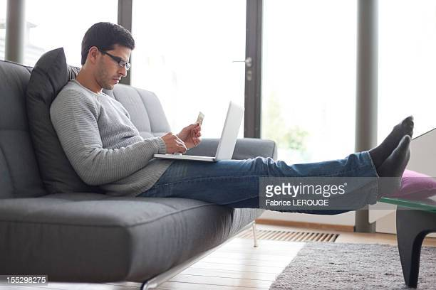 Man holding a credit card and using a laptop
