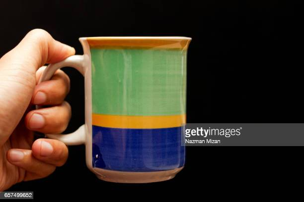 A man holding a cup of coffee on black background.