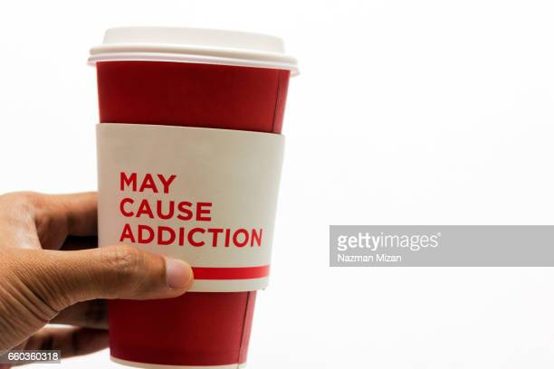 A man holding a cup of coffee with addiction warning. Health concept.