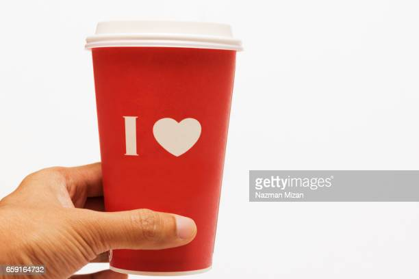 A man holding a cup of coffee with love symbol.