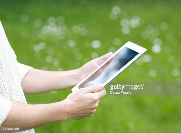 man holding a digital tablet in the countryside - newtechnology stock pictures, royalty-free photos & images