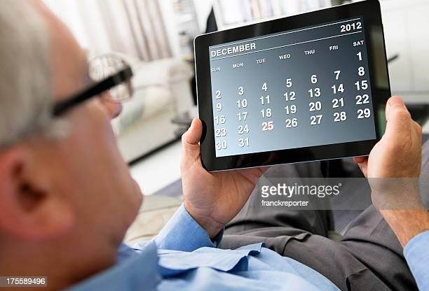 Man holding a digital tablet with December 2012 calendar