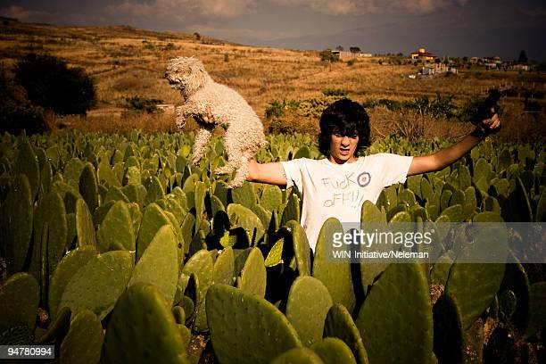 man holding a dog and a handgun, cocoyoc, mexico - ornamental plant stock pictures, royalty-free photos & images