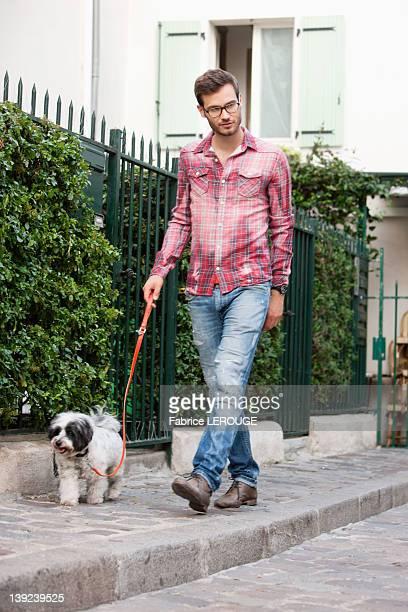 man holding a dog on leash walking on a sidewalk, paris, ile-de-france, france - un seul homme photos et images de collection