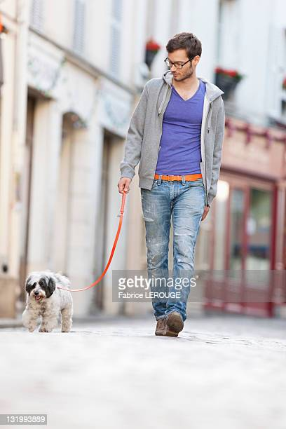 Man holding a dog on leash walking on the street, Paris, Ile-de-France, France