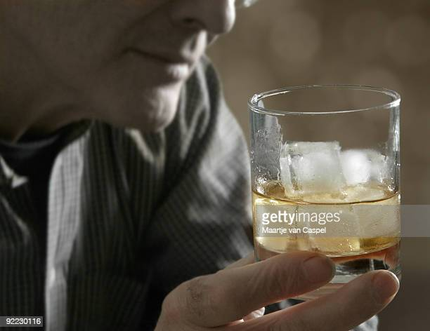 A man holding a drink with ice cubes