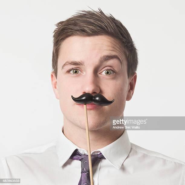 Man holding a false moustache to his face