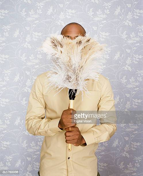 Man Holding a Feather Duster in Front of His Face