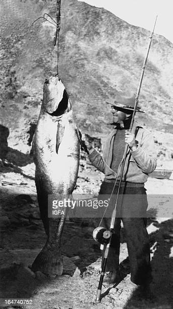 A man holding a fishing rod stands next to a 685 pound white seabass caught near the Coronado Islands in Mexico on June 13 1937