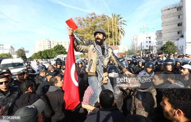 A man holding a flag and a red card from Tunisia's 'Fech Nestannew' youth movement attends a protest against high cost of living after the new budget...