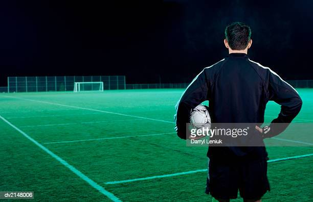 Man Holding a Football and Looking Out Over an Empty Football Pitch