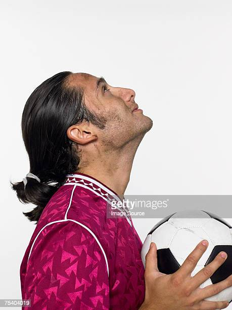 Man holding a football and looking up