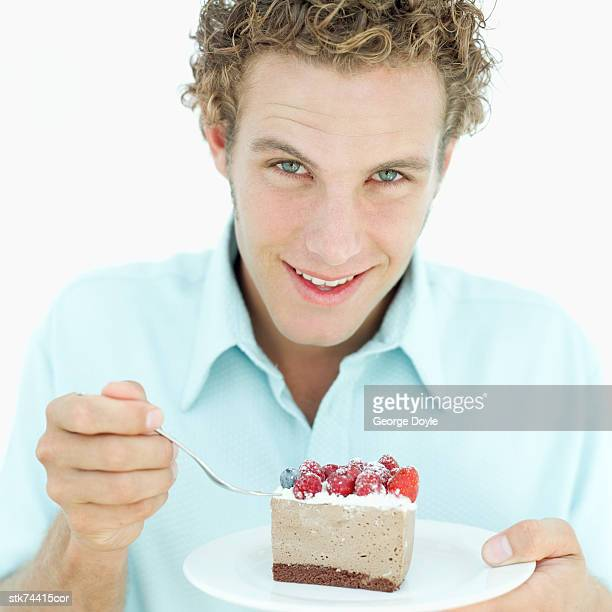 man holding a fork and a slice of mousse cake on a plate