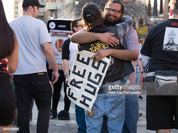 "Man holding a ""free hugs"" sign embraces a stranger on 6th Street in Austin, Texas during SXSW 2013"